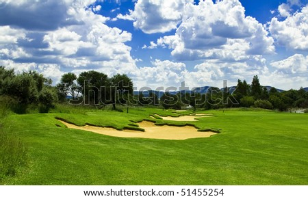 Golf course with green grass sand traps(bunkers) and river in the distance with a perfect sky - stock photo
