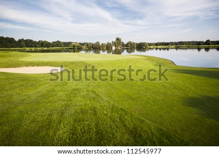 Golf course with green, sand trap and lake with cloudscape in background. - stock photo