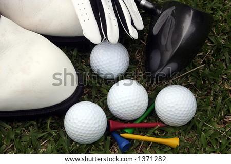 Golf equipment laying on grass - stock photo