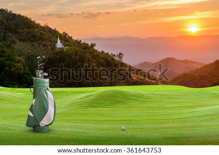 golf equipment on green and hole as background - stock photo