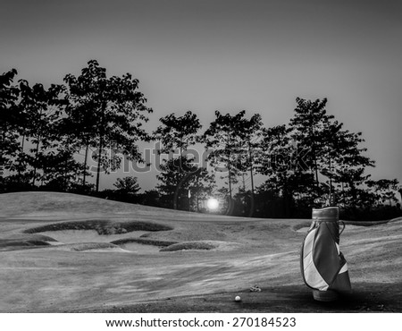 golf equipment on green and hole as background. black and white - stock photo