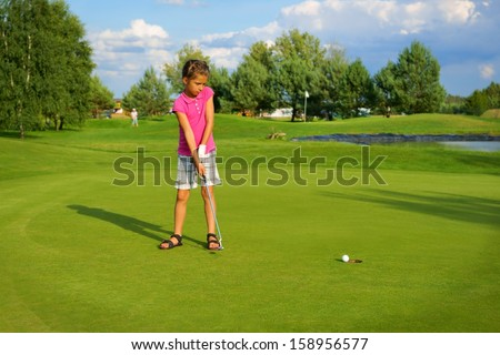 Golf, girl golfer driving ball into the hole - stock photo