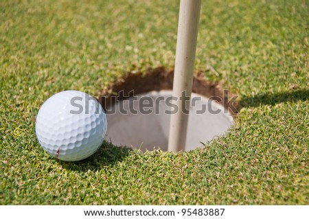 golf hole with ball and flag - stock photo
