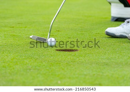 Golf man putting on green - stock photo