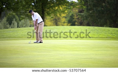 Golf player concentrating for putting golf ball on green. - stock photo