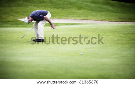 Golf player convulsed with laughter after ball just missed hole. - stock photo