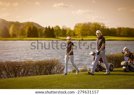 Golf player couple walking on fairway with beautiful lake in background at sunset. - stock photo