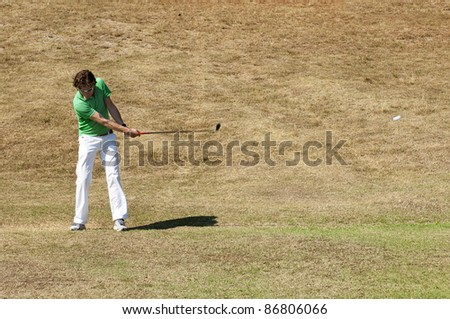 Golf player hitting his ball on the fairway of a golf course - stock photo