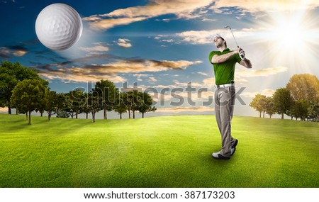 Golf Player in a green shirt taking a swing, on a golf course. - stock photo