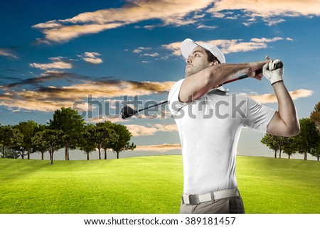 Golf Player in a white shirt taking a swing, on a golf course. - stock photo