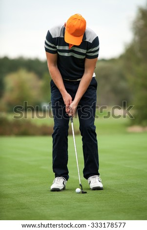 Golf player preparing for a putt on the golf green - stock photo