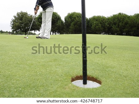 Golf player putting ball in hole - stock photo
