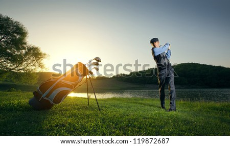 Golf player strikes the ball strongly - stock photo