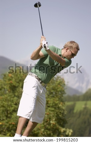 Golf player teeing off - stock photo