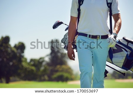 Golf player walking and carrying bag on course during summer game golfing - stock photo