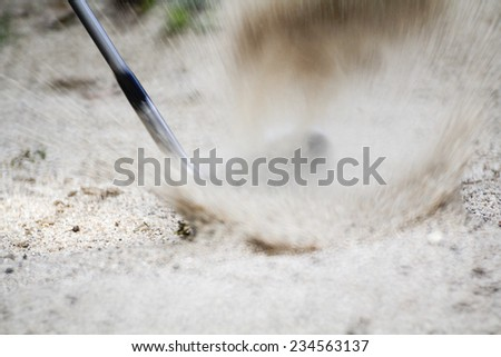Golf sand wedge hitting in trap - stock photo