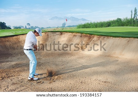 golf shot from sand bunker golfer hitting ball from hazard - stock photo