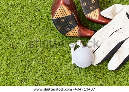 Golf sport tools on green grass background.Golf ball, glove, tee and old wood golf clubs on the green grass background.Outdoor sport concept. - stock photo