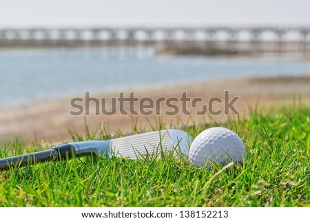 Golf stick and ball on grass with a background of nature. Close-up. - stock photo