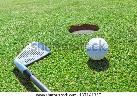 Golf stick and ball on the grass near the hole. - stock photo