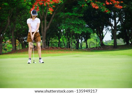 Golf woman player green putting - stock photo