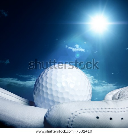 golfball on a glove with a bright sun in the background - stock photo