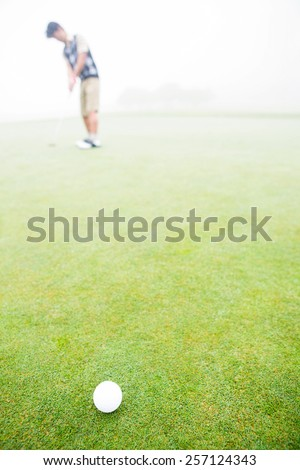 Golfer about to tee off on a sunny day at the golf course - stock photo