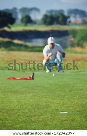 Golfer aiming lining up putt on green - stock photo