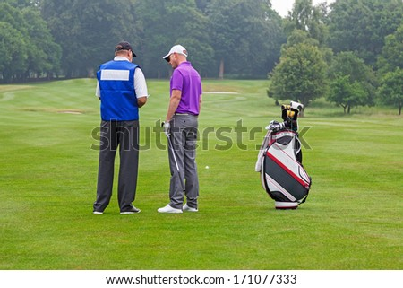 Golfer and caddy on the fairway of a par 4 reading the course guide for club selection. - stock photo