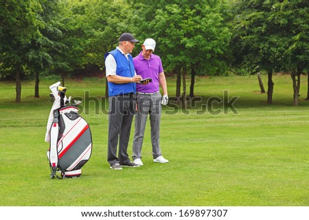 Golfer and caddy standing on the fairway of a par 4 looking at a course guide. - stock photo