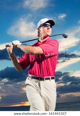 Golfer at sunset, Man swinging golf club with dramatic sunset sky backdrop - stock photo