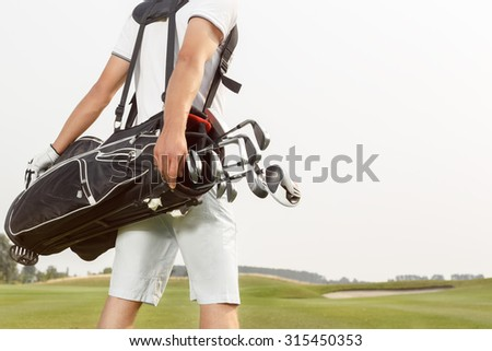 Golfer carrying his golf bag across a golf course - stock photo