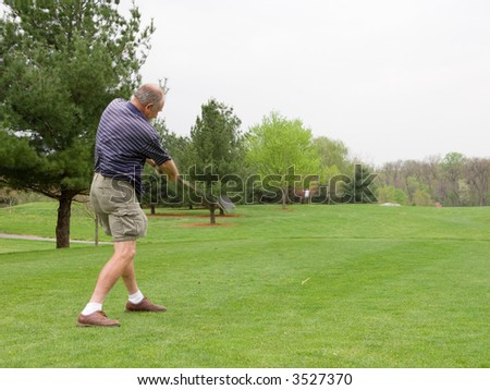 Golfer crushing a golf ball off the tee. This scene is FILLED with action: motion blur on the club, ball rocketing up into the air, and the tee flipping below it. 1 of 3 high speed series. - stock photo