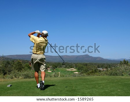 Golfer driving golf ball on beautiful golf course with clear blue sky in the mountains - stock photo