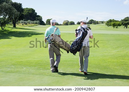 Golfer friends walking holding their golf bags on a sunny day at the golf course - stock photo