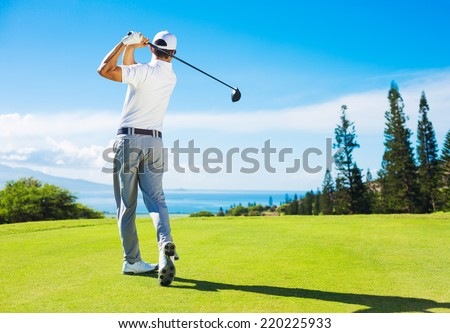 Golfer Hitting Ball with Club on Beatuiful Golf Course - stock photo