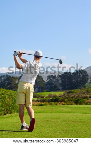 golfer hitting driver off tee box - stock photo