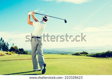 Golfer Hitting Golf Shot with Club on Beautiful Golf Course on Vacation - stock photo