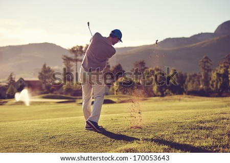 Golfer hitting golf shot with club on course while on summer vacation - stock photo