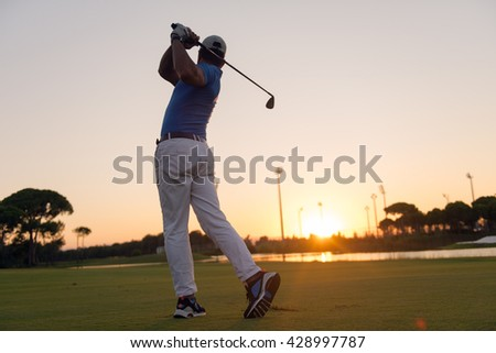 golfer hitting long shot with driver on course at beautiful sunset - stock photo