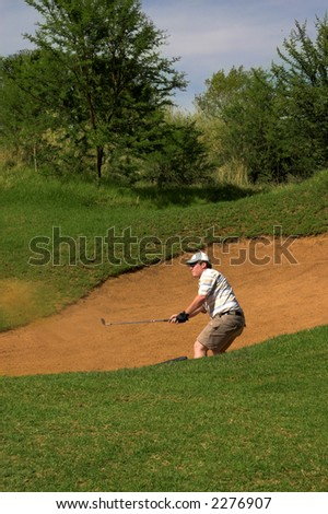 Golfer hitting the ball out of the sand bunker. Sand and golf club are in motion - stock photo