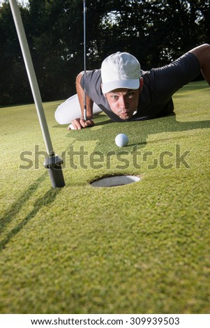 Golfer lying down on the green, blowing on his white ball to make it fall in the hole. Close up  on the ball and the man head with a beautiful forest in the background. - stock photo
