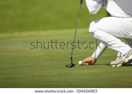 golfer marks his position on a green  - stock photo