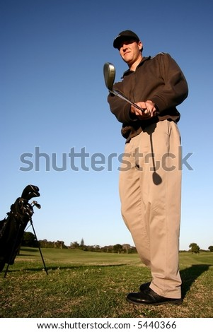Golfer on fairway following the flight of his ball towards the green - stock photo