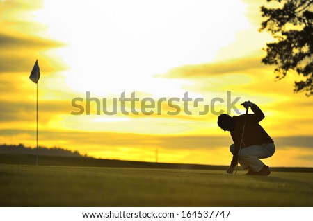 golfer on green backlit sunset - stock photo