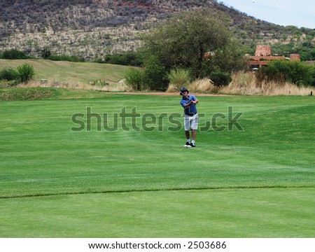 Golfer on the South African golf course pitching the ball onto the green. Golf club is in motion and the ball is in the air. - stock photo