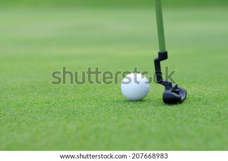 Golfer on training putt golf ball - stock photo