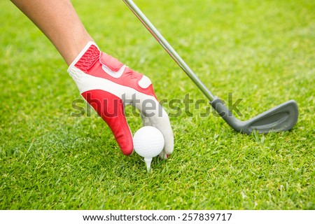 Golfer placing golf ball on tee at the golf course - stock photo