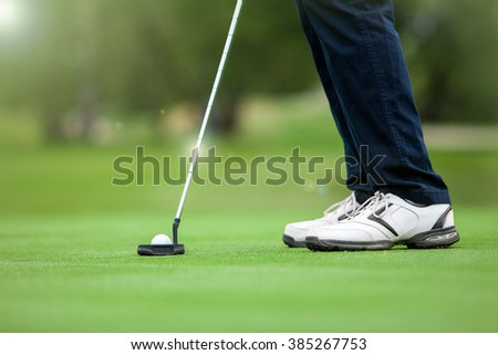Golfer preparing for a putt on the green. - stock photo