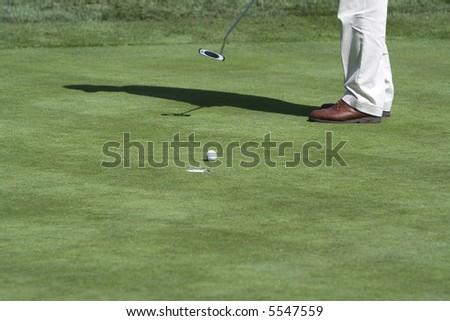 Golfer putting (ball by hole) - stock photo